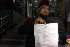 Ketua Umum Cyber Indonesia, Muannas Alaidid, memperlihatkan surat laporan polisi terhadap musisi Erdian Aji Prihartanto alias Anji dan Hadi Pranoto terkait dugaan penyebaran berita bohong atau hoaks obat Covid-19 di Mapolda Metro Jaya, Senin (3/8/2020). (Antara)