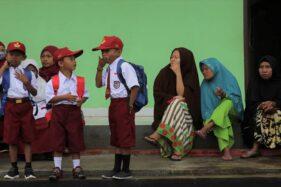 Sejumlah orang tua murid menunggu anaknya saat bersekolah pada hari pertama tahun ajaran baru di SD Negeri 1 Praja Taman Sari di Desa Wonuamonapa, Konawe, Sulawesi Tenggara, Senin (13/7/2020). Pihak sekolah terpaksa menerapkan pembelajaran dengan tiga kali pertemuan tatap muka di sekolah dalam sepekan karena terbatasnya jaringan telekomunikasi untuk penerapan pembelajaran jarak jauh secara daring guna mencegah persebaran Covid-19. (Antara Foto–Jojon)