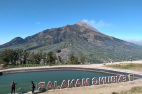 Pengunjung Embung Manajar berfoto di sekitar embung, berlatar belakang Gunung Merapi, Sabtu (1/8/2020). (Solopos/Bayu Jatmiko Adi)