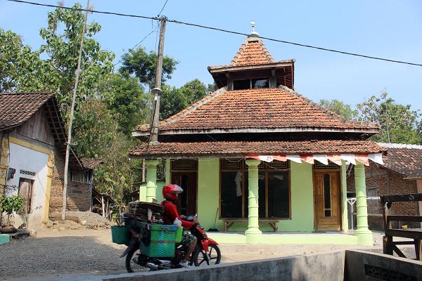 Seorang warga melintas di depan musala tanpa nama yang berdiri dan menjadi batas wilayah Jawa Tengah dan Jawa Timur di Dukuh Dadok RT 010/RW 002, Desa Glonggong, Gondang, Sragen, Rabu (5/8/2020). (Solopos/Tri Rahayu)