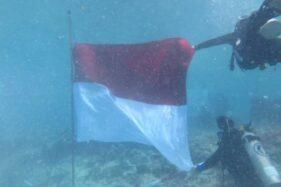 Penyelam sedang mengimbarkan bendera Merah Putih di kawasan Pulau Bando, Sumbar. (Antaranews.com)