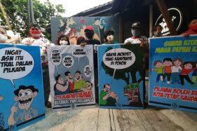 Sukarelawan pendukung Gibran Rakabuming Raka yang tergabung dalam komunitas Kancane Gibran Gaess (Kagege) menunjukkan empat karikatur karya kartunis Solo yang menyerukan pelaksanaan Pilkada Solo yang damai, Rabu (5/8/2020) sore, di Ngopi Serius, Purwosari, Laweyan. (Solopos/Kurniawan)