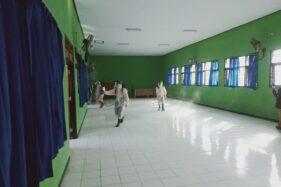 Petugas dari BPBD Kabupaten Madiun menyemprot ruangan SMPN 1 Dolopo dengan cairan disinfektan setelah ditemukan satu guru di sekolah tersebut positif Covid-19, Senin (3/8/2020). (Istimewa/BPBD Madiun)