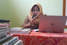 Guru Kelas VI SDN 1 Balerejo, Kecamatan Kebinsari, Kabupaten Madiun, Anifatul Maghfiroh, mengajar siswanya dengan menggunakan handy talky atau HT, Senin (10/8/2020). (Abdul Jalil/Madiunpos.com)