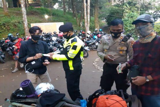 Kapolsek Tawangmangu, AKP Ismugiyanto, (mengenakan jaket polisi), mengecek kelengkapan protokol kesehatan milik pendaki di jalur pendakian Cemara Kandang, Sabtu (15/8/2020). (Istimewa/Dokumentasi Polsek Tawangmangu)