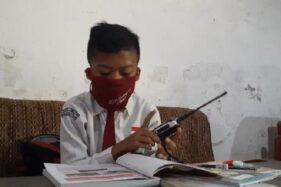 Seorang siswa di SDN 1 Balerejo belajar dengan memanfaatkan HT di salah satu rumah temannya di Desa Balerejo, Kecamatan Kebonsari, Kabupaten Madiun, Jawa Timur, Senin (10/8/2020). (Abdul Jalil/Madiunpos.com)