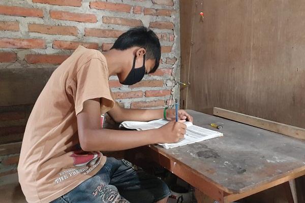 Wahyu Agus Nurtino, 12, siswa kelas VI SDN Brumbun, Kecamatan Wungu, Kabupaten Madiun saat sedang belajar di rumahnya, Desa Brumbun, Selasa (4/8/2020). (Abdul Jalil/Madiunpos.com)