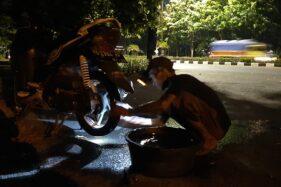 Paimin menambal ban sepeda motor di lapaknya dekat SPBU Manahan, Jl Adisucipto, Solo, Jumat (11/9/2020) dini hari. (Solopos/Kurniawan)