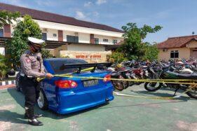 Kanit Patwal Satlantas Polres Karanganyar, Ipda Marindra Prasetya, memasang garis polisi pada mobil Toyota Corolla Altis yang diparkir di halaman Mapolres Karanganyar pada Selasa (22/9/2020).  (Solopos.com/Sri Sumi Handayani)
