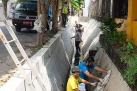 Warga yang tidak memakai masker membersihkan selokan di Jl. Muh. Yamin, Kecamatan Serengan, Solo, Selasa (22/9). (Solopos/Nicolous Irawan)