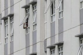 Pasien Covid-19 melambaikan tangan dari salah satu kamar di Rumah Sakit Darurat Penanganan Covid-19 Wisma Atlet Kemayoran, di Jakarta. (Antara-Ariella Annasya)
