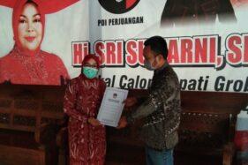 Komisioner KPU Grobogan Divisi Teknis Penyelenggaraan Suwiknyo menyerahkan salinan penetapan pasangan calon kepada calon bupati Grobogan Sri Sumarni (kiri), Rabu (23/9/2020) sore.(Istimewa/KPU Grobogan)