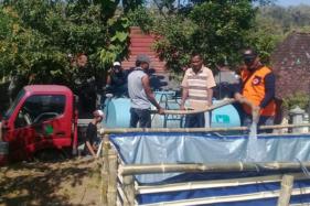 Sejumlah petugas Badan Penanggulangan Bencana Daerah (BPBD) Sukoharjo menyalurkan air bersih dari mobil tangki ke bak penampungan air bersih yang terbuat dari terpal di Desa Ngreco, Kecamatan Weru, Kamis (24/9/2020). (Istimewa/Tohir)