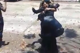 Kepsek di Garut digotong petugas lantaran mencoba kabur. (Tangkapan layar video)