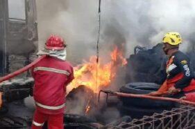 Petugas pemadam kebakaran berusaha memadamkan api yang membakar garasi Bus Cendana yang ada di Jalan Raya Madiun-Ponorogo, Kelurahan Demangan, Kecamatan Taman, Kota Madiun, nyaris ludes terbakar, Selasa (29/9/2020). (Istimewa)