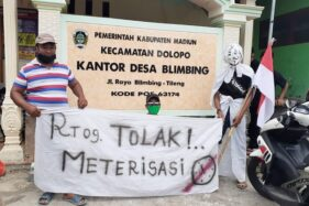 "Warga membentangkan spanduk yang bertuliskan ""Tolak Meterisasi"" terkait rencana pemerintah yang ingin melakukan pengelolaan sumber air bersih di Desa Blimbing, Kecamatan Dolopo, Kabupaten Madiun, Senin (28/9/2020). (Abdul Jalil/Madiunpos.com)"