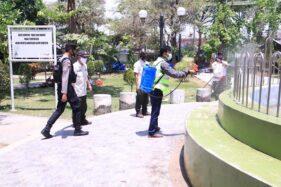 Seorang warga disanksi menyemprot Taman Kota Caruban, Kabupaten Madiun, karena tidak mengenakan masker, Rabu (16/9/2020). (Istimewa/Polres Madiun)