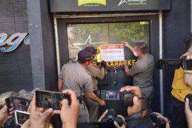 Petugas Satpol PP Kota Madiun memasang segel di pintu tempat hiburan malam In Lounge Pub dan Karaoke di Jl. Bali, Senin (21/9/2020). (Abdul Jalil/Madiunpos.com)