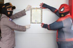 Kasatbinmas Polresta Solo AKP Febriyani Aer (kiri) menempel salinan maklumat Kapolri ditemani tokoh superhero Spiderman di kawasan Selter Manahan, Solo, Rabu (30/9/2020) siang. (Istimewa/Humas Polresta Solo)