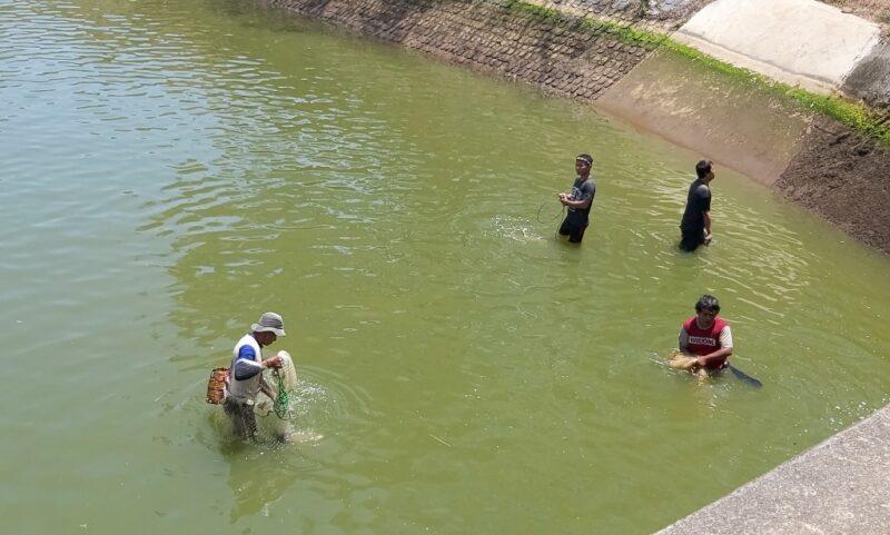 Warga mencari ikan dialiran Dam Colo Nguter setelah dilakukan penutupan pada Minggu (11/10/2020). (Solopos.com/Indah Septiyaning W.)