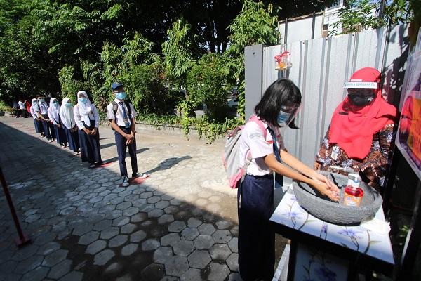 Siswa kelas IX SMP Negeri 4 Solo antre dengan menjaga jarak saat mencuci tangan sebelum memasuki kelas pada Simulasi Pembelajaran Tatap Muka (PTM) di halaman SMP Negeri 4, Solo, Selasa (13/10/2020). (Solopos/Nicolous Irawan)