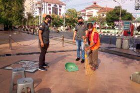 Seorang warga yang kedapatan tidak mematuhi protokol kesehatan pencegahan Covid-19 tengah menyapu atau membersihkan pedestrian di depan Balai Kota Semarang, Jumat (16/10/2020). (Semarangpos.com-Satpol PP Semarang)