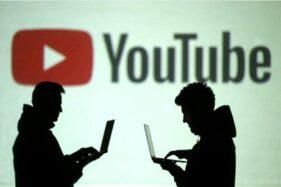 Siluet pengguna perangkat mobile terlihat di sebelah proyeksi layar logo Youtube. (Reuters-Dado Ruvic)