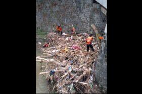 Sukarelawan membersihkan tumpukan material sampah yang tersangkut pada pilar jembatan Banaran, Grogol, Sukoharjo, Minggu (25/10/2020). (Istimewa/Sukarelawan Sukoharjo)