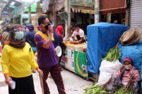 Lurah Pasar Bunder Sugino bersama nakes Sri Harsiyah mengajak para pedagang dan pembeli menggunakan masker dengan benar di Pasar Bunder Sragen, Jumat (23/10/2020). (Solopos-Tri Rahayu)