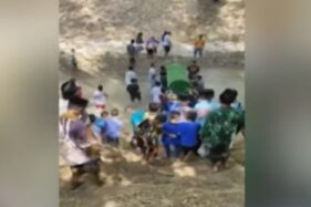 Tangkapan layar video viral warga Ponorogo menggotong keranda melewati sungai.
