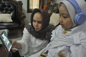 Siswa sekolah dasar mengikuti pembelajaran jarak jauh (PJJ) dengan sistem online pada hari pertama tahun ajaran baru 2020-2021 di Palembang, Sumatra Selatan dengan didampingi orang tuanya, Senin (13/7/2020). (Antara-Feny Selly)