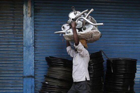Seorang pekerja membawa sejumlah knalpot mobil di pasar suku cadang otomotif. (Bisnis-Reuters-Adnan Abidi)
