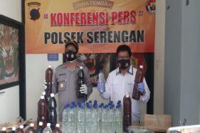 Kapolsek Serengan Kompol Suwanto (kiri) menunjukkan minuman keras (miras) jenis ciu yang disita Polsek Serengan dalam razia rutin selama dua bulan terkahir di Mapolsek Serengan pada Selasa (24/11/2020). (Istimewa/Dokumen Polresta Solo)