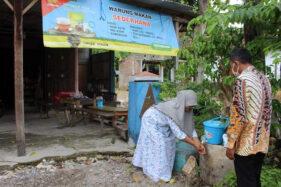 Sekretaris Desa Katelan Paidi (kanan) mengedukasi warga pemilik warung agar rajin cuci tangan dengan ember bantuan desa lewat program satu rumah satu ember di Dukuh Brakbumder, Desa Katelan, Tangen, Sragen, Rabu (25/11/2020). (Solopos/Tri Rahayu)