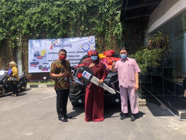 Pemimpin Bank Jateng Cabang Koordinator Surakarta, Djaka Nur Sahid (kiri), menyerahkan mobil Mitsubishi Xpander kepada pemenang pengundian Tabungan Bima Rina Setyowati (tengah) di Kantor Bank Jateng Solo, Kamis (19/11/2020). (Solopos/Ichsan Kholif Rahman)