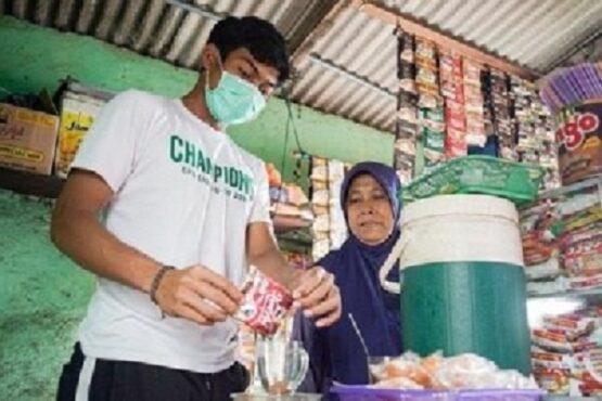 Andhika Ramadhani mewujudkan mimpi sambil membantu ibunya menjaga warung kopi (warkop). (Persebaya.id)