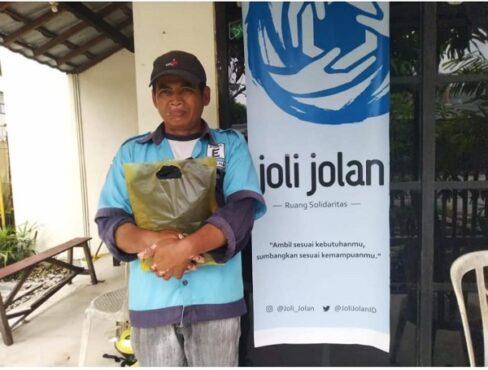 Seorang juru parkir mendapat jaket gratis hasil kiriman kurir JNE di Ruang Solidaritas Joli Jolan, Solo, beberapa waktu lalu. (Solopos.com/Chrisna Chanis Cara)