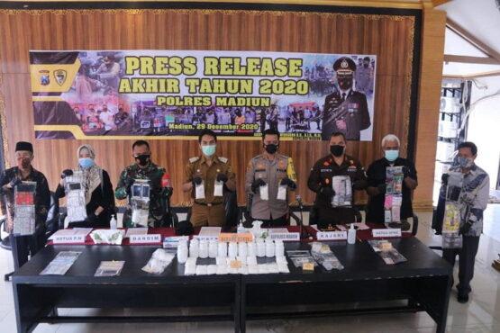 Kapolres Madiun, AKBP Bagoes Wibisono beserta Bupati Madiun Ahmad Dawami dan sejumlah pejabat menunjukkan barang bukti dalam pers rilis akhir tahun Polres Madiun tahun 2020, Selasa (29/12/2020). (Istimewa/Polres Madiun)