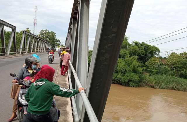 Warga berkerumun di tepi Jembatan Sapen untuk menyaksikan lokasi warga diduga menceburkan diri ke Sungai Bengawan Solo, Jumat (4/12/2020). (Solopos-Moh. Khodiq Duhri)