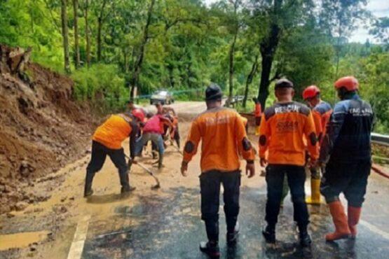 Tim gabungan sukarelawan di Kabupaten Karanganyar membersihkan material bekas tanah longsor di jalan utama menuju kawasan wisata Tawangmangu melalui Karangpandan pada Minggu (6/12/2020). (Istimewa/Dokumentasi Sukarelawan Solopeduli, Endhy Yudha)