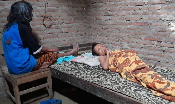 Kadiman, 35, terbaring di ranjang ditemani ibunya, Ny. Dasir, di rumahnya yang berlokasi di tanah tegalan tak jauh dari hutan Perhutani di Desa Jenar, Kecamatan Jenar, Sragen, Sabtu (16/1/2021). (Istimewa/Iwan)