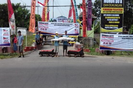 Dua orang warga membopong pocong di antara dua nisan di depan Perlintasan Siboto, Kalimacan, Kalijambe, Sragen, Minggu (17/1/2021). (Istimewa/warga Siboto)