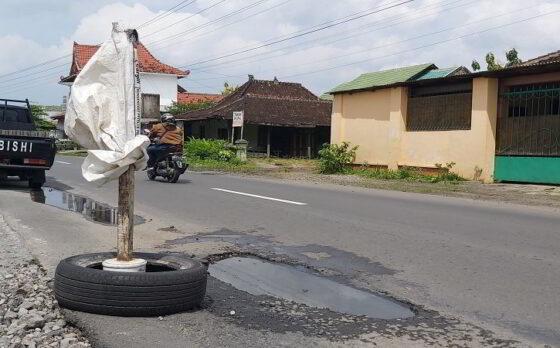 Sebuah ban bekas diletakkan di dekat jalan berlubang di ruas Mojolaban-Sukoharjo. Warga menaruh ban bekas sebagai rambu jika kondisi jalan berlubang. Foto diambil Selasa (26/1/2021). (Solopos.com/Indah Septiyaning Wardani)