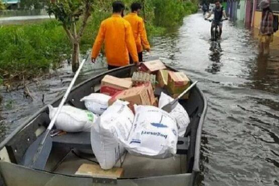Para anggota BPBD Kota Banjarmasin, Kalsel, Rabu (20/1/2021) menggunakan perahu saat mengantar bantuan untuk warga terdampak banjir. (Antara)