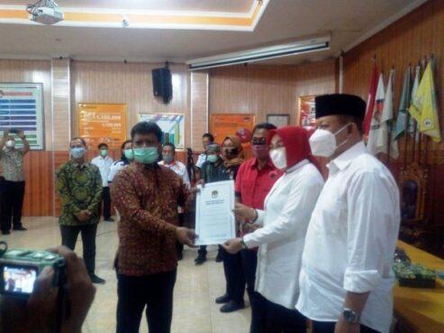 Ketua KPU Grobogan Agung Sutopo (kiri) menyerahkan berita acara penetapan bupati-wabup terpilih Pilkada 2020 kepada Sri Sumarni-Bambang Pujiyanto di aula KPU, Kamis (21/1/2021). (Solopos.com/Arif Fajar Setiadi)