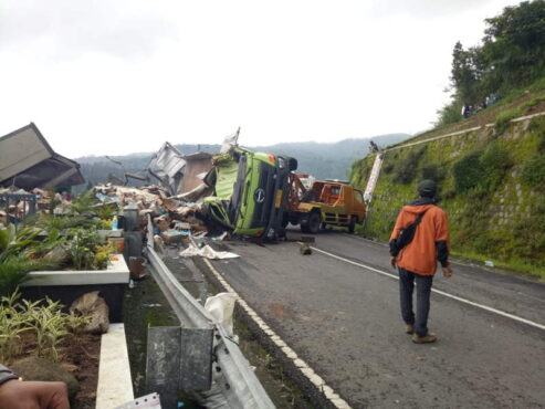 Mobil derek berupaya mengevakuasi truk tronton bermuatan minuman isotonik yang terjungkal di jalan tembus Magetan-Tawangmangu, tepatnya di depan RM Legender pada Jumat (22/1/2021) pukul 04.05 WIB. (Istimewa/Dokumentasi Polres Karanganyar)