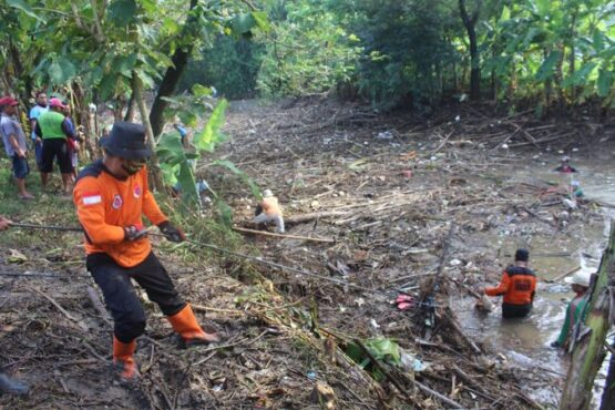 Sukarelawan SAR bersama warga dan TNI berusaha menarik sampah yang sudah diikat tali dadung dari sungai ke daratan di Dam Buk Bubrah, Dukuh Plosokerep, Desa Bandung, Ngrampal, Sragen, Minggu (24/1/2021). (Solopos/Tri Rahayu)