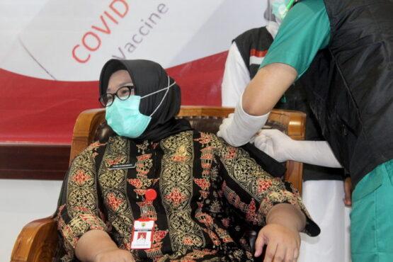 Bupati Yuni Sukowati memalingkan mukanya saat dokter menyuntikan vaksin Sinovac ke lengannya saat pencanangan vaksinasi di RSSP Sragen, Senin (25/1/2021). (Solopos.com/Tri Rahayu)