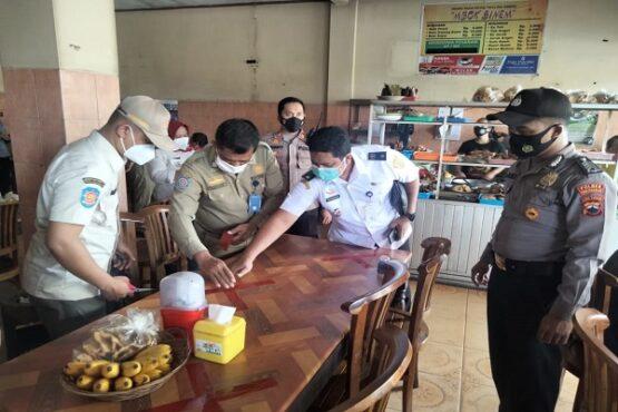 Anggota Satuan Tugas (Satgas) Penanganan Covid-19 Kecamatan Sukoharjo memasang lakban jaga jarak di warung pecel di Kecamatan Sukoharjo, Rabu (13/1/2021). (Solopos/Bony Eko Wicaksono)
