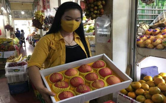 Staf kios buah Sari Buah di Pasar Gede menunjukkan apel tato yang banyak dicari untuk keperluan Tahun Baru Imlek, Jumat (29/1/2021). (Farida Trisnaningtyas/Solopos)